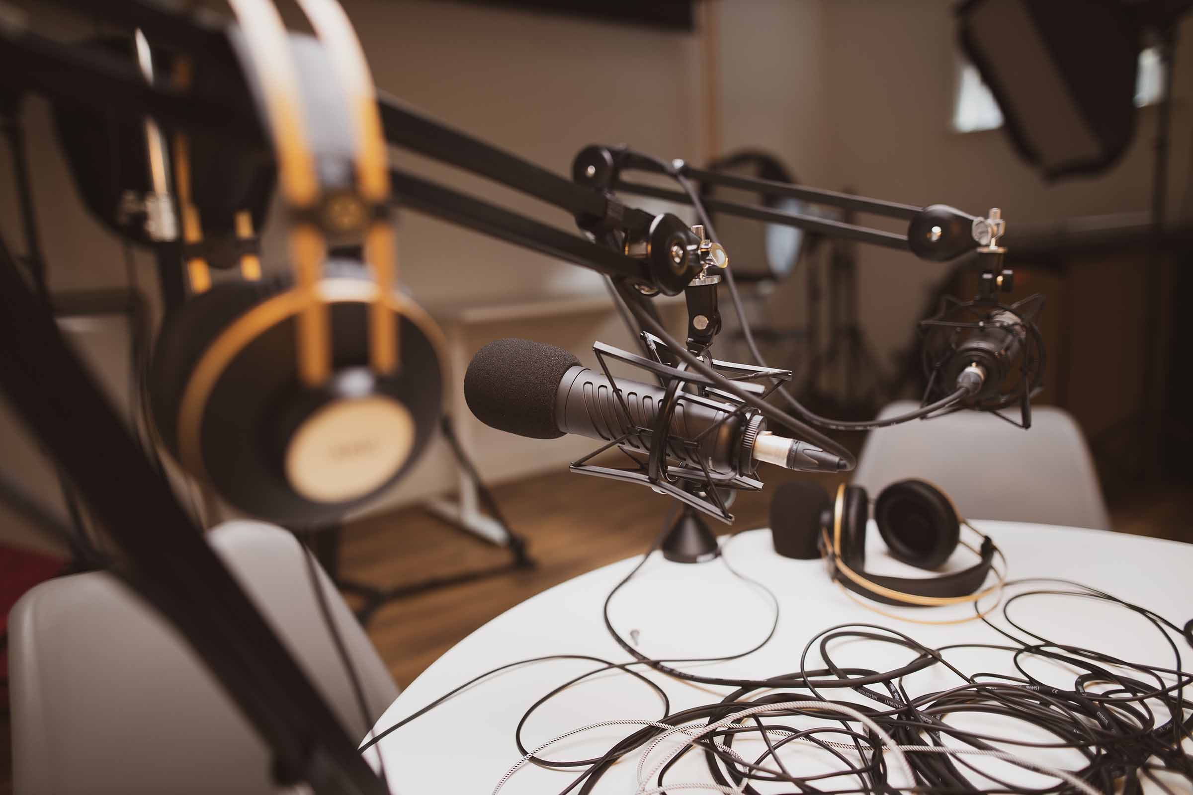 A podcast production style setup with microphone and headphones on a table