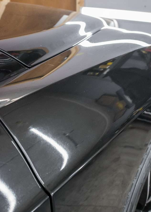 Close up shot of Bentley Flying Spur car with scratches on front wing