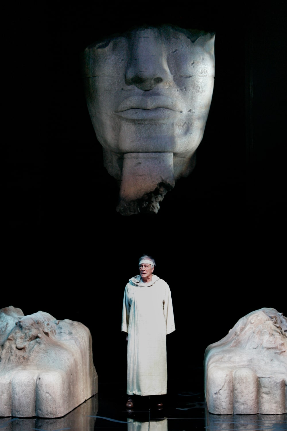 Old man in white robe stands starkly light in front of Sphinx.