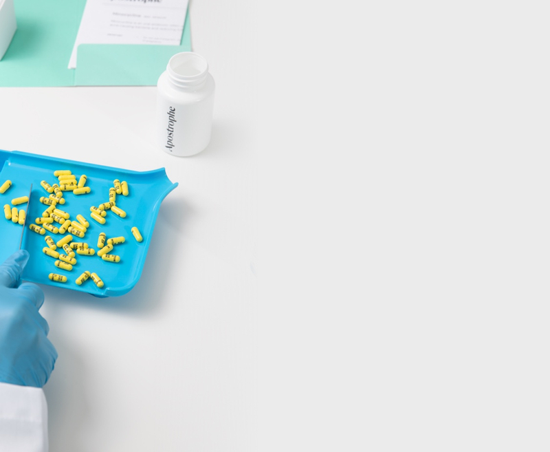 Top of desktop page image containing yellow pills being sorted on a blue tray by our pharmacist.