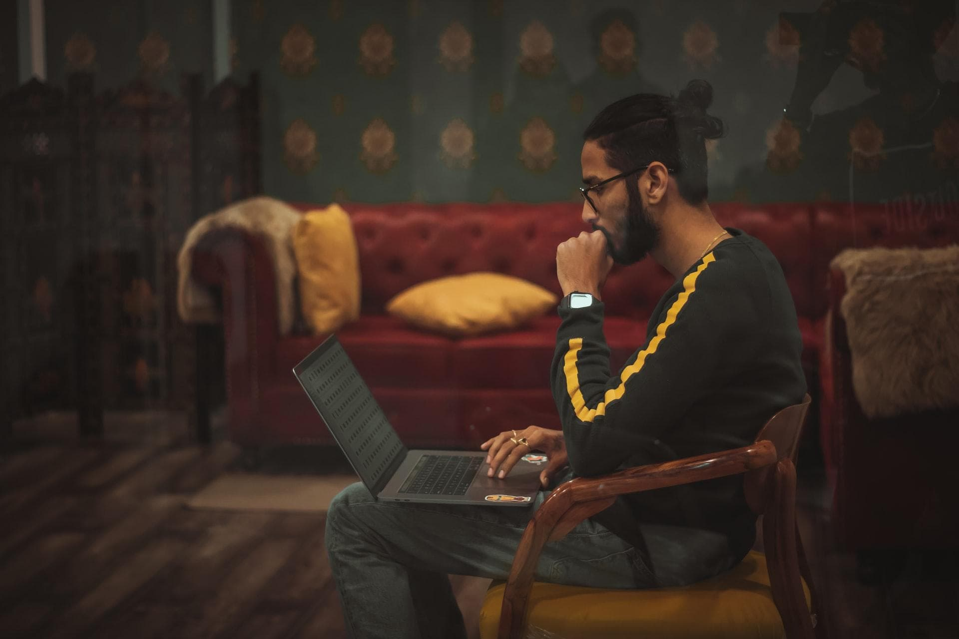 man sitting on wooden chair while using laptop computer on lap