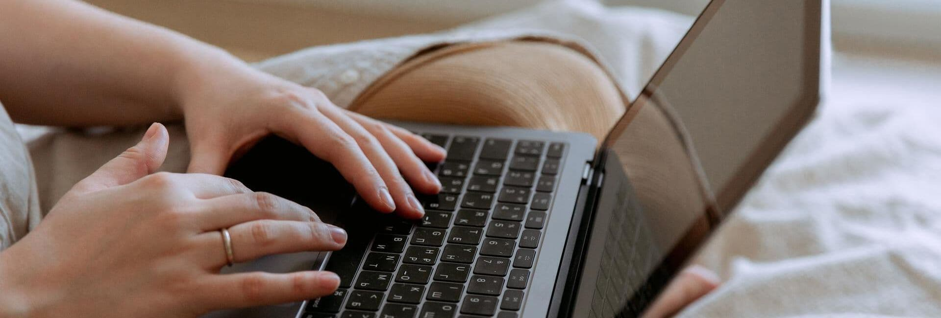 Teilnehmerin mit Laptop während einer Live-Online Schulung auf ihrem Sofa