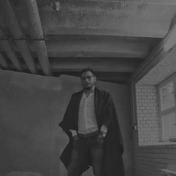 Sexy queer man in a black poncho. Avant garde fashion. Haute de couture. Tribal postapocaliptic fashion.