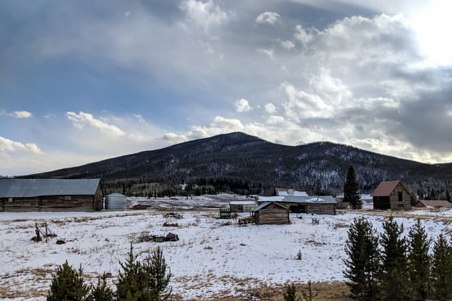 Looking out across a snowy high country ranch. A small mountain rises behind the ranch buildings.