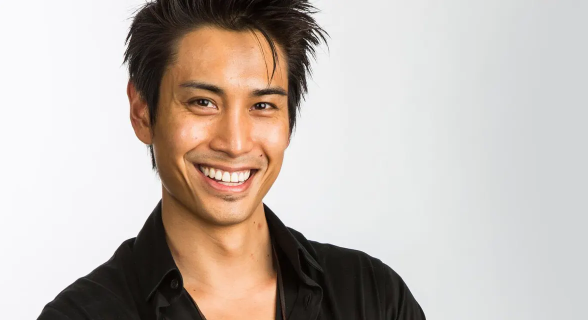 Anthony Kongphan smiles in black button-down in front of white background