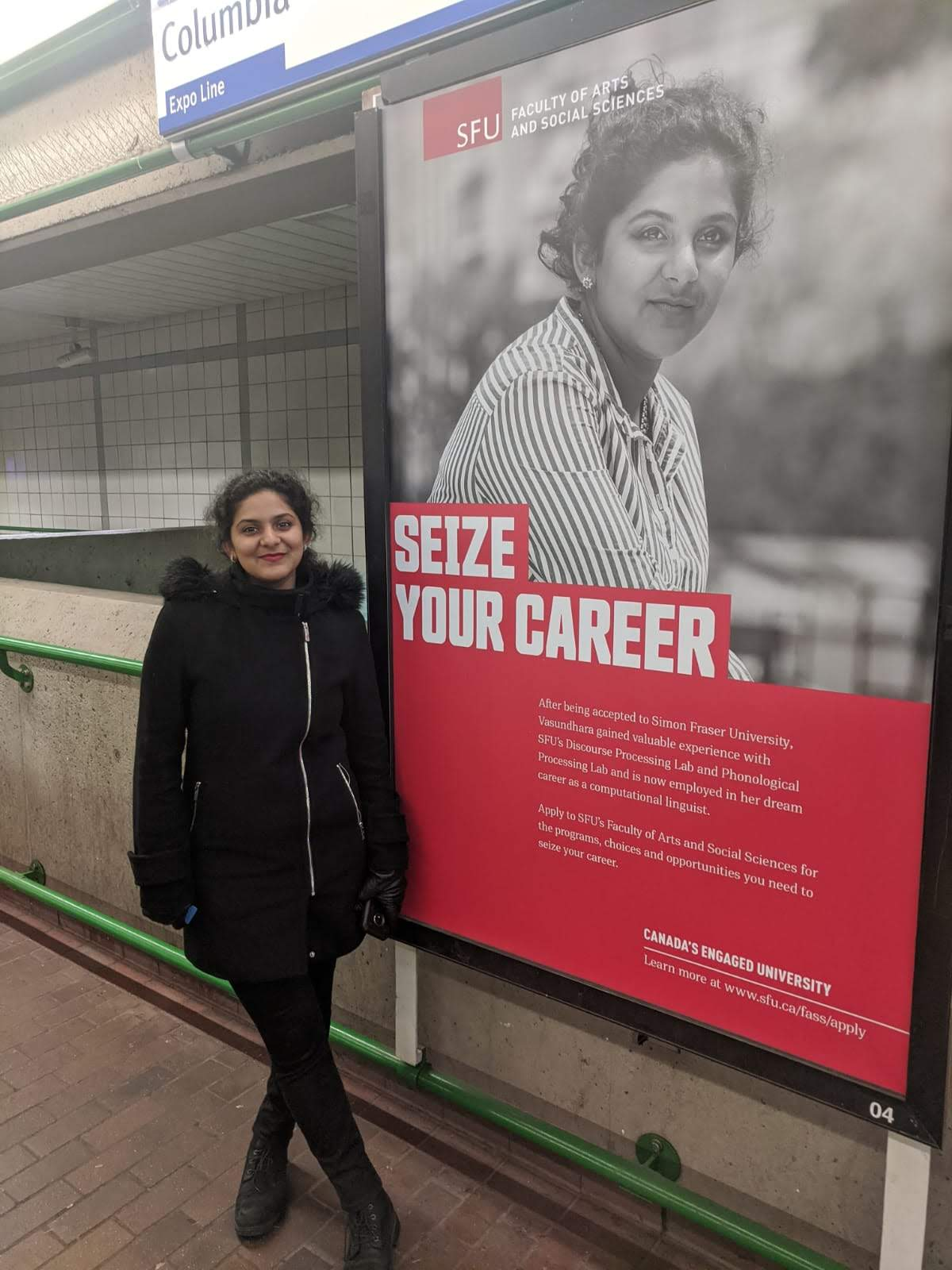 Vasundhara standing in a SkyTrain station beside a large advertisement for Simon Fraser University's Faculty of Arts and Social Sciences. The advert has a black-and-white photograph of xem in it, and the words 'Seize Your Career' in big, bold text, followed by two paragraphs of small text talking about xyr career trajectory and why readers should apply to the Faculty of Arts and Social Sciences.