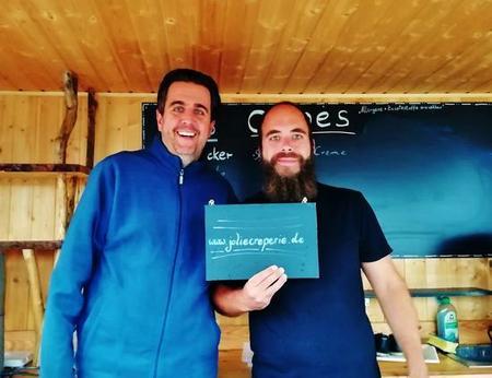 Bastian Pastewka und ein Catering Mitarbeiter lächeln im Creperie Foodtruck in die Kamera