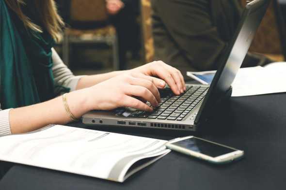 vrouw die typt achter laptop of tafel