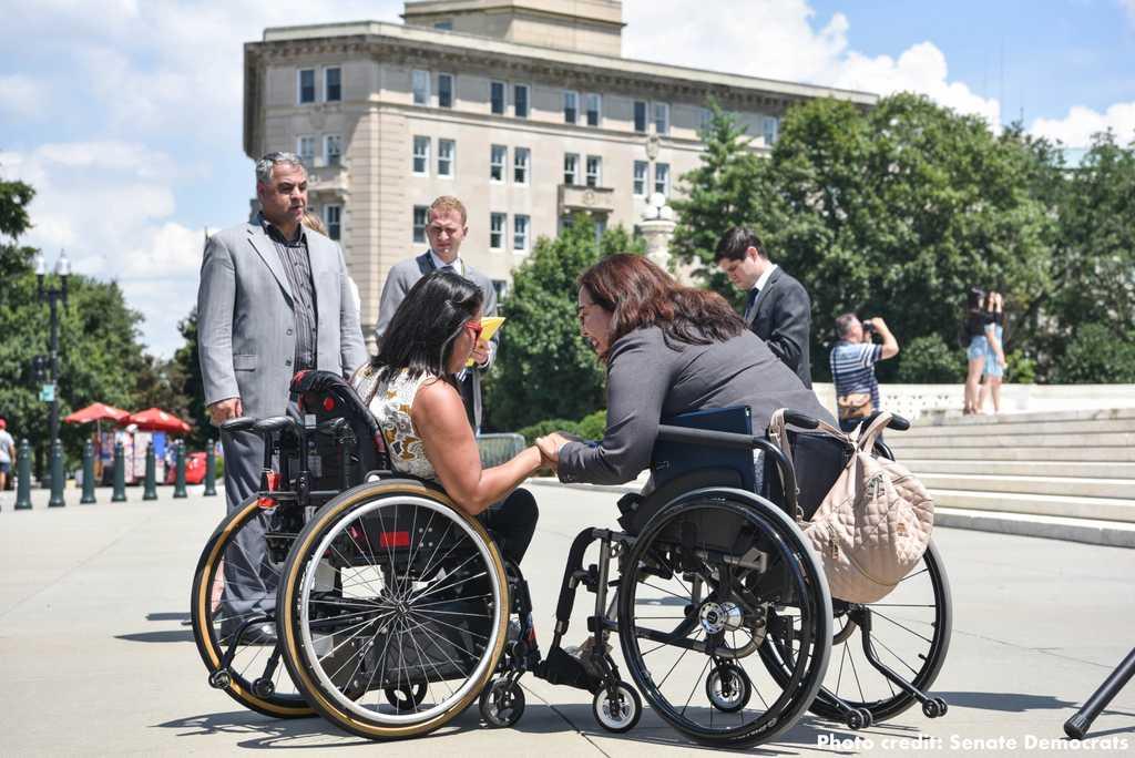 Wheelchair-using Senator Tammy Duckworth meets with activists.