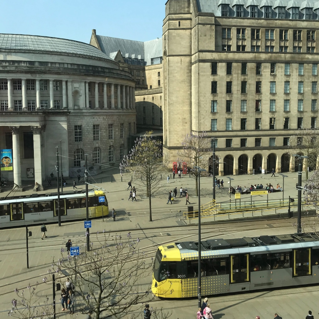 St Peter's Square in Manchester, you can see old buildings, people walking and trams