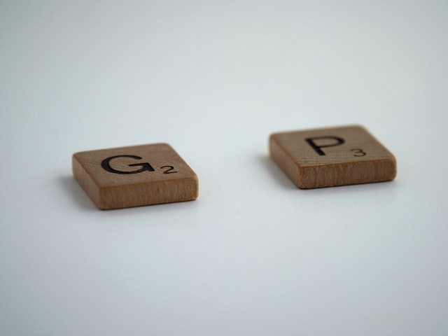 brown wooden dice on white, letters g and p