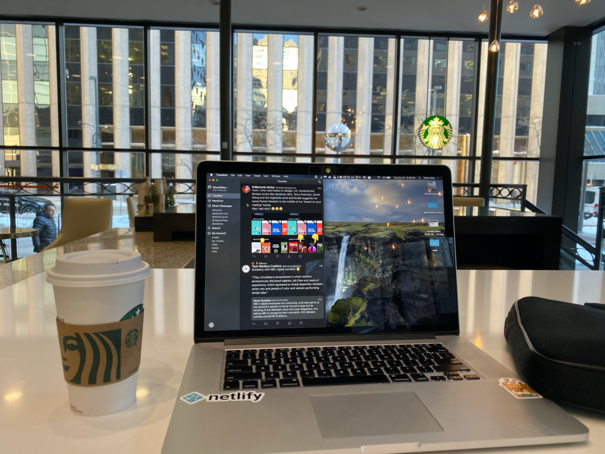 A view of the hotel from an area in the lobby that folks can relax and do remote work from in a small meeting area on the main lobby floor showing a cup of Starbucks coffee next to my MacBook Pro looking out at the street from the hotel into downtown Denver.