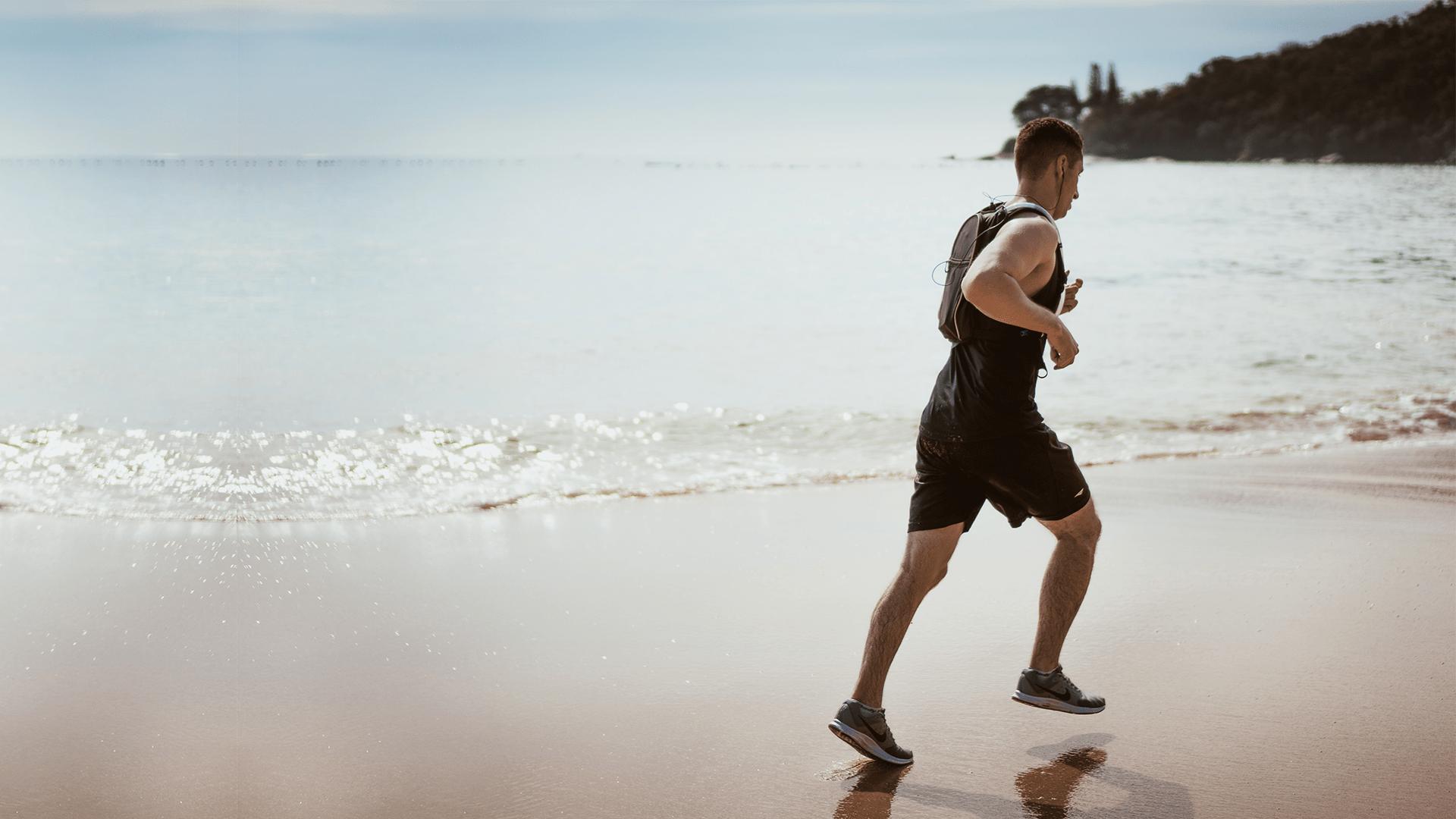 athletic man running on a beach