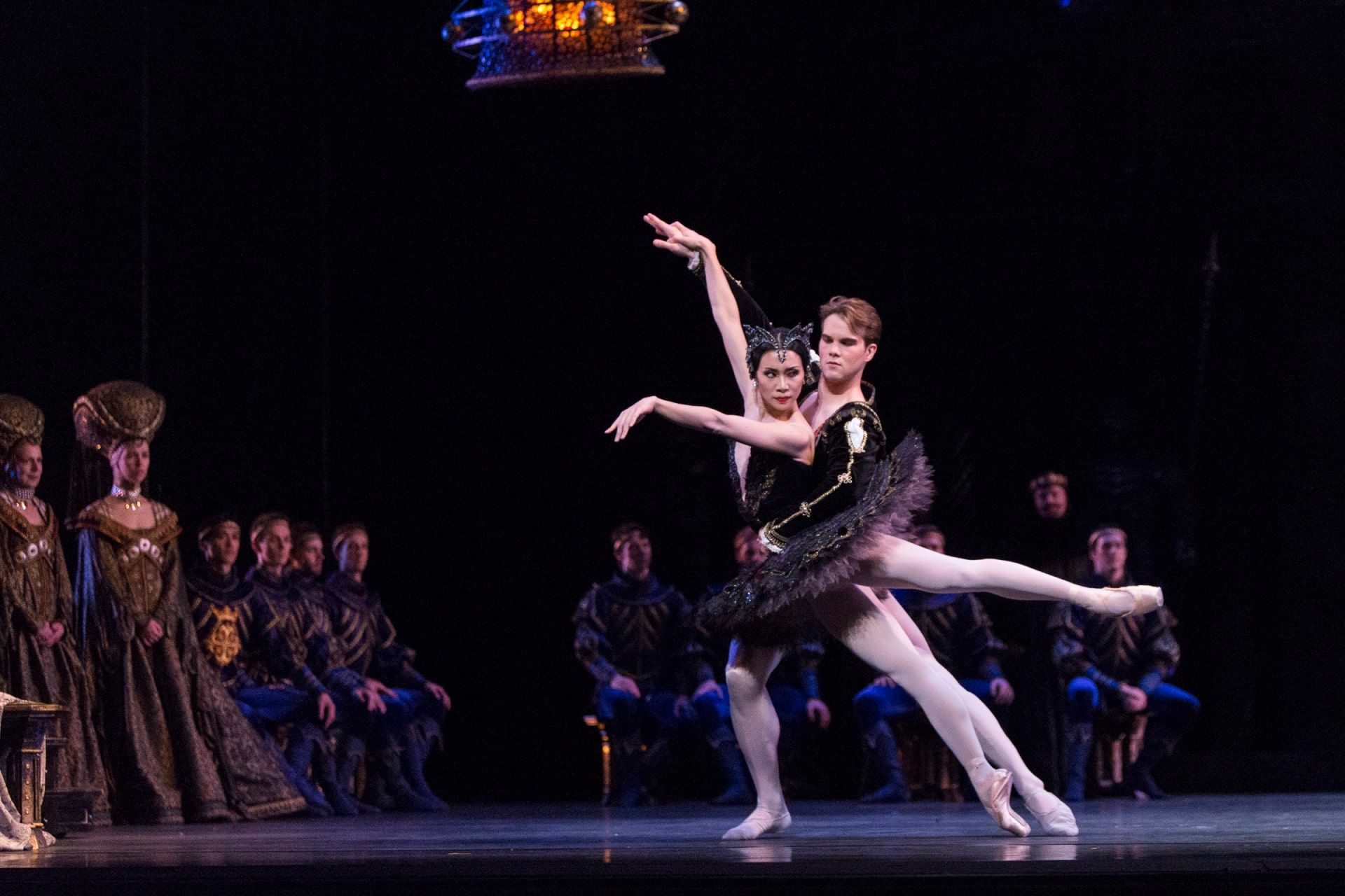 Ballerina in black tutu dances with partner, watched by blue-lit seated courtiers in regal attire.