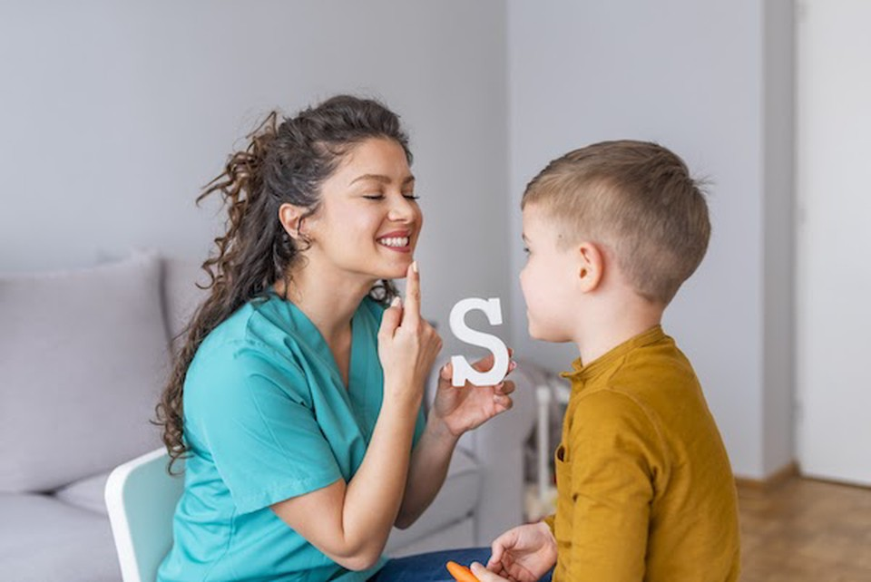 """A speech-language pathologist practices sounding out the letter """"S"""" with a child."""