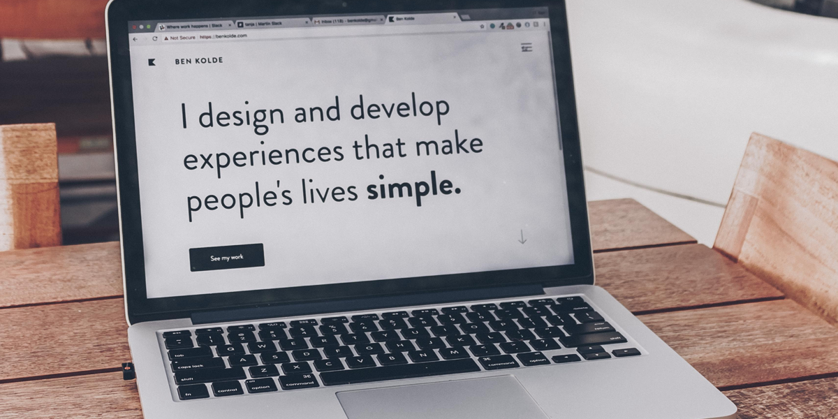 Open laptop featuring a black and white homepage for a UI design portfolio