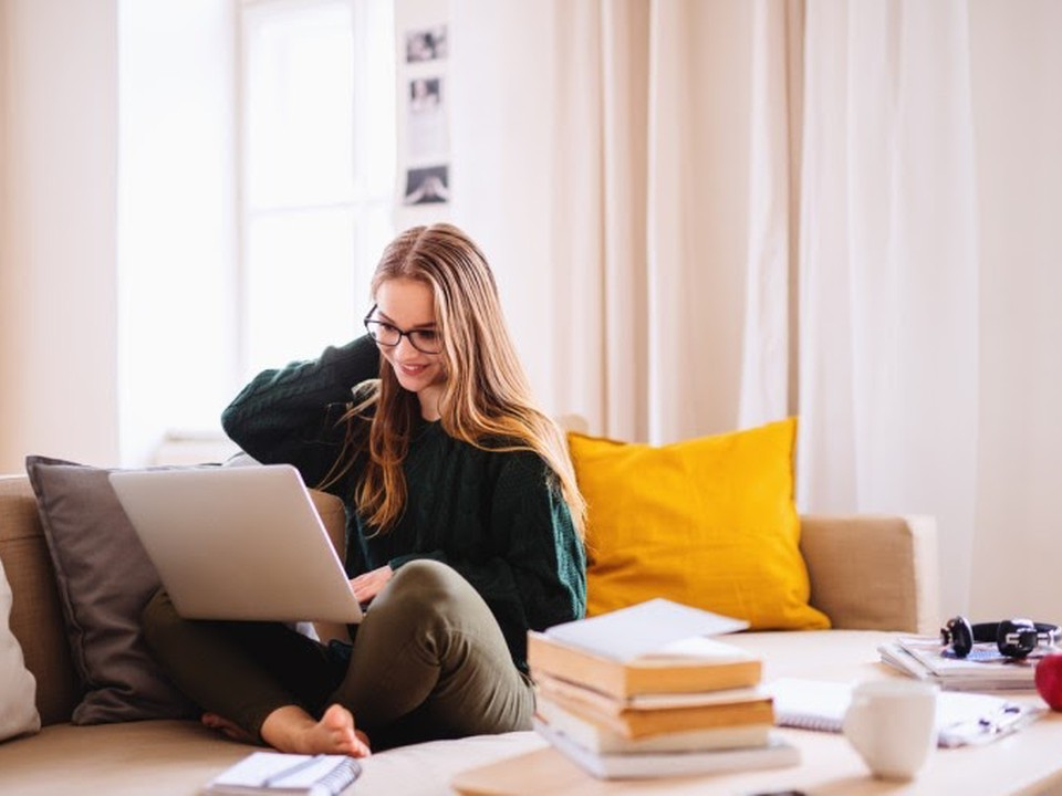 A smiling college student surrounded by books and notebooks sits on a sofa using a laptop.