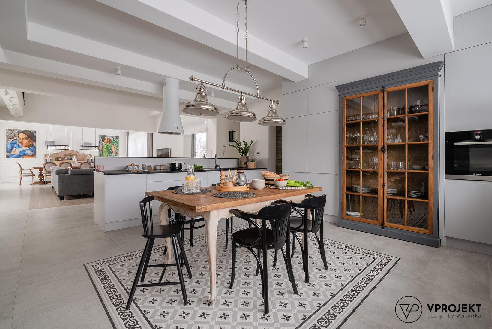 Wnętrze kuchni ze strefą jadalnianą, salon na drugim planie