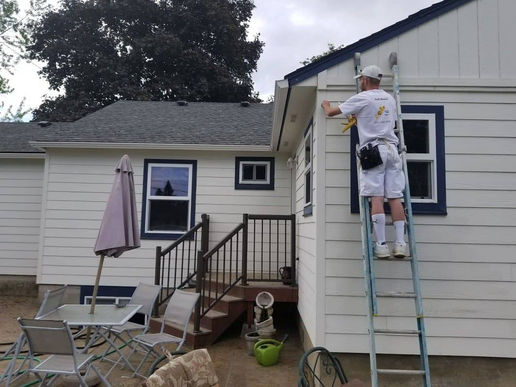 enlarged photo of man on ladder painting a white home