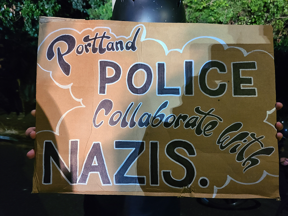 A handmade sign reflects on Portland Police Bureau's history of collaborating with the wrong side of history as well as the law.