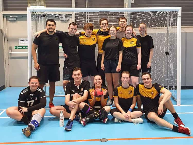 Myself with the University of York handball team, 13 of us in total, in two rows, smiling for the camera in front of one of the handball goals, following our 2nd game of the season.