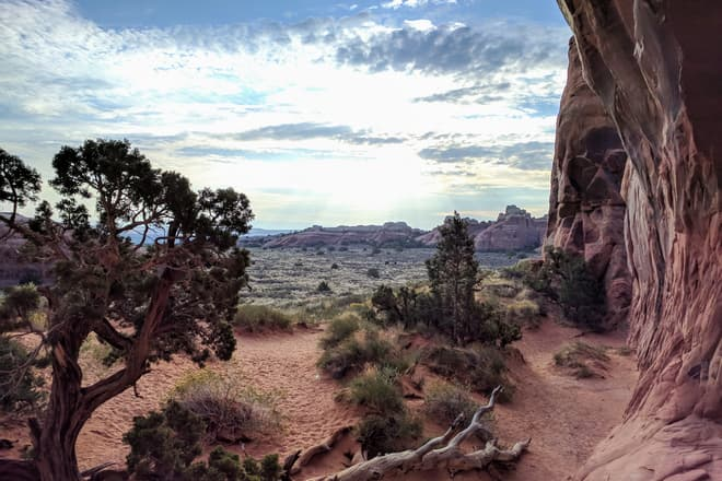 An oblique view through Pine Tree Arch in Arches National Park towards the rising sun. Unusually shaped sandstone mounds and pillars can be seen in the distance.