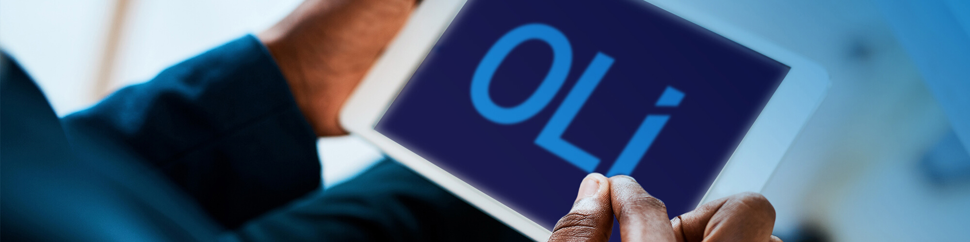 person holding tablet with word OLI on screen