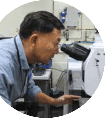 Gary Peng staring through a microscope