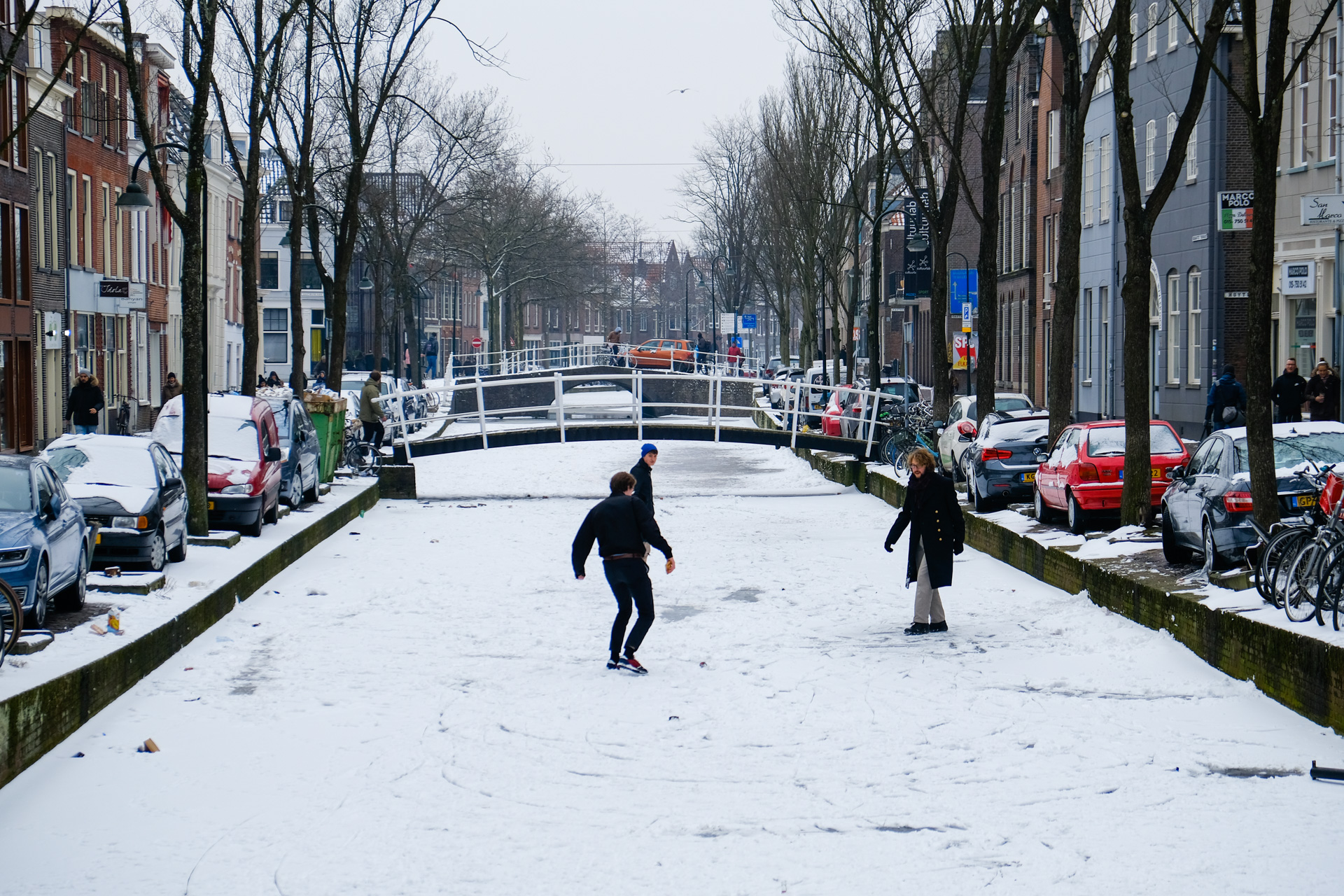 Some guys are playing and walking on the frozen canal