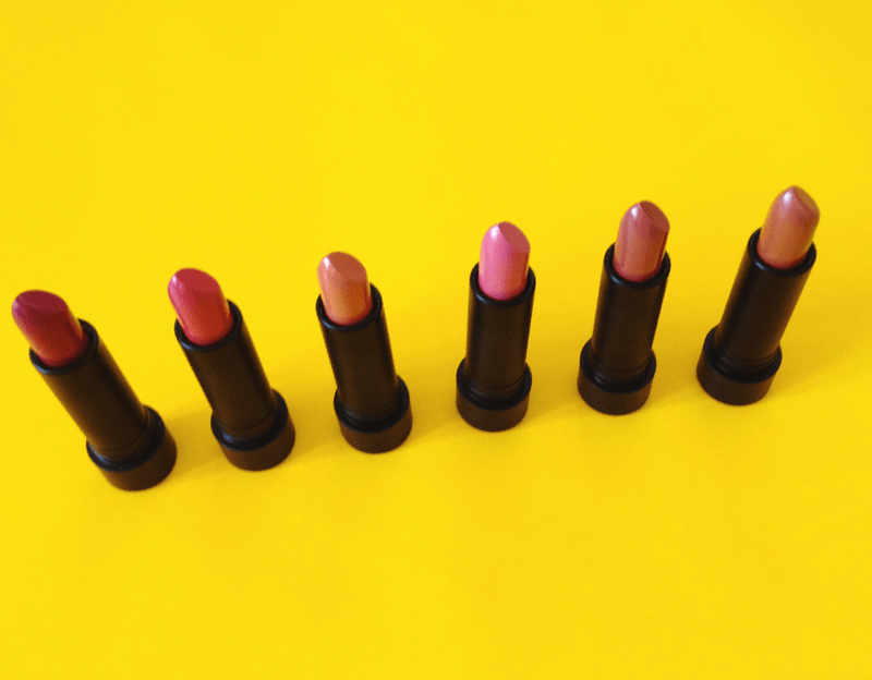 Pink lipsticks lined up on yellow background.