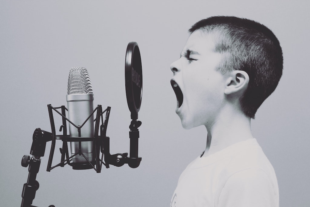 Kid screaming at a microphone - Photo by Jason Rosewell on Unsplash