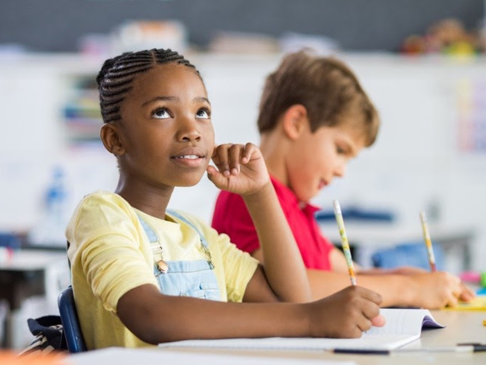 An elementary school student looks up from their notebook.