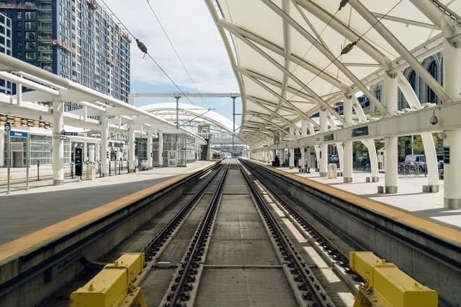 A view straight down the train tracks at the Denver Union Station light rail stop. The tracks are shaded on the right by a long canopy made of white canvass and steel.
