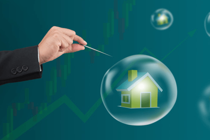 A pin pricking a bubble around a home signifying a stock market bubble