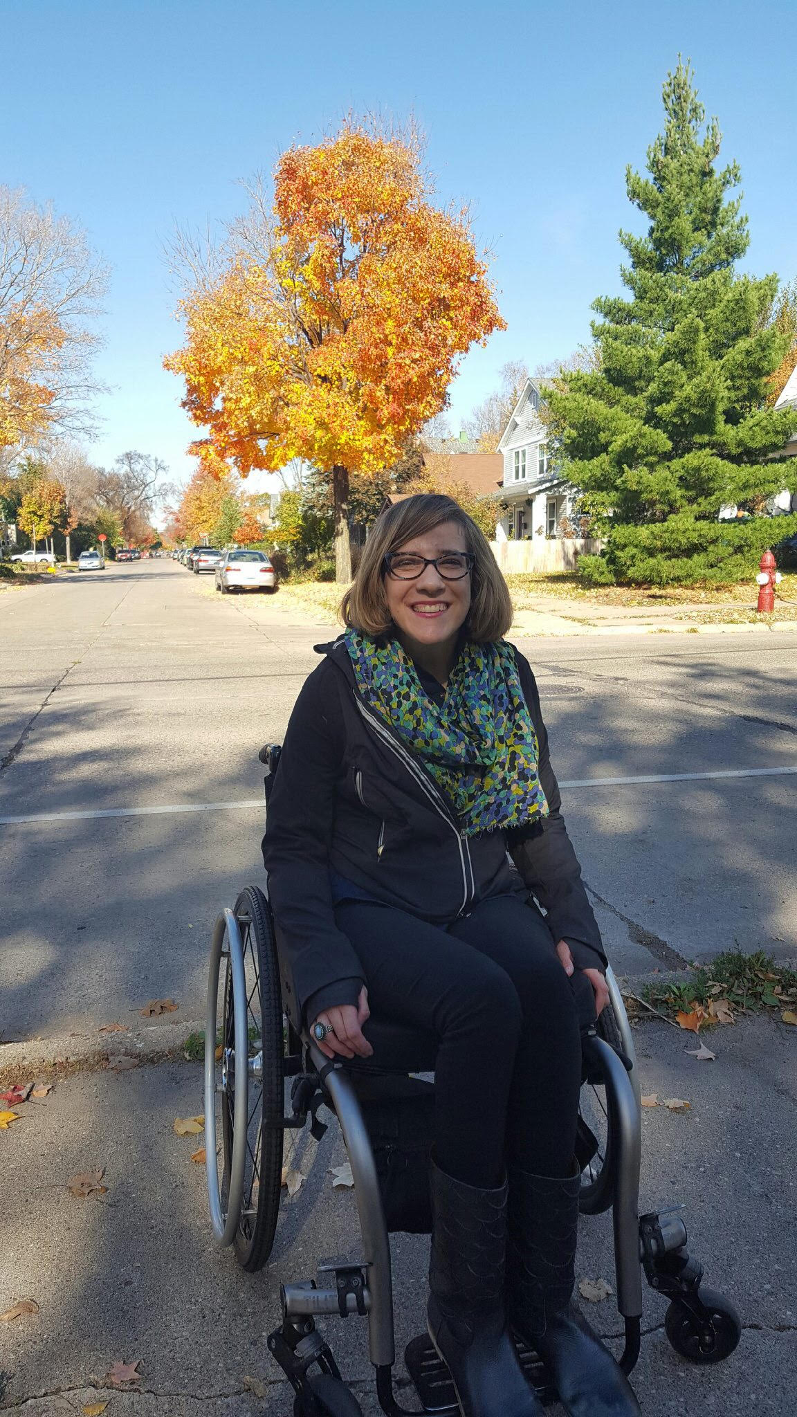 Claire Forrest smiling and sitting in wheelchair on curb outside