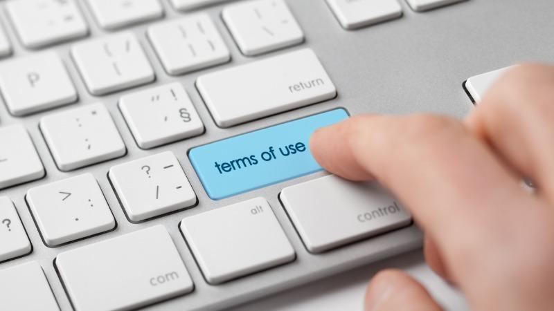 Eine Computertastatur, auf der eine Hand die eingefügte Taste für Nutzungsrechte drückt.