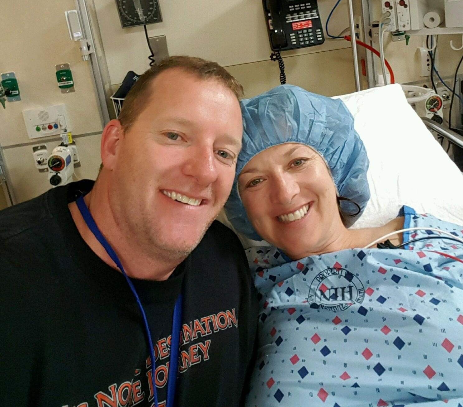 Melinda on her hospital bed, smiling, with her husband at her side, also smiling