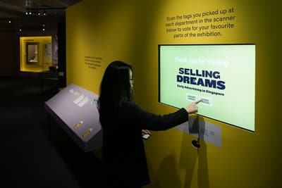 A woman interacts with a screen embedded into a wall, with a RFID reader slot below it. The wall reads: 'Scan the tags you picked up at each department in the scanner below to vote for your favourite parts of the exhibition'.