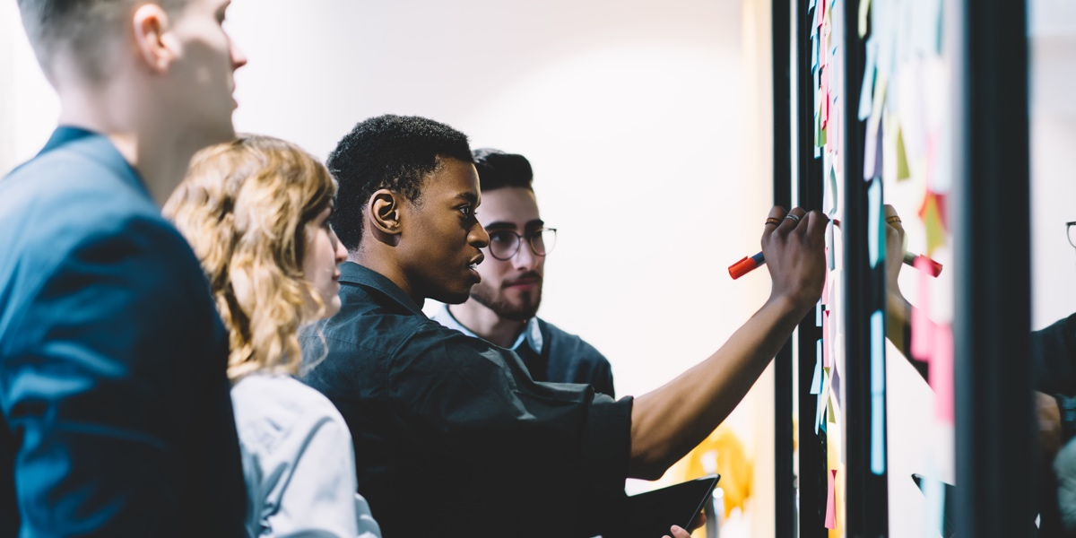 Group of UX designers gathered around a whiteboard with sticky notes, watching one designer sketch their ideas out