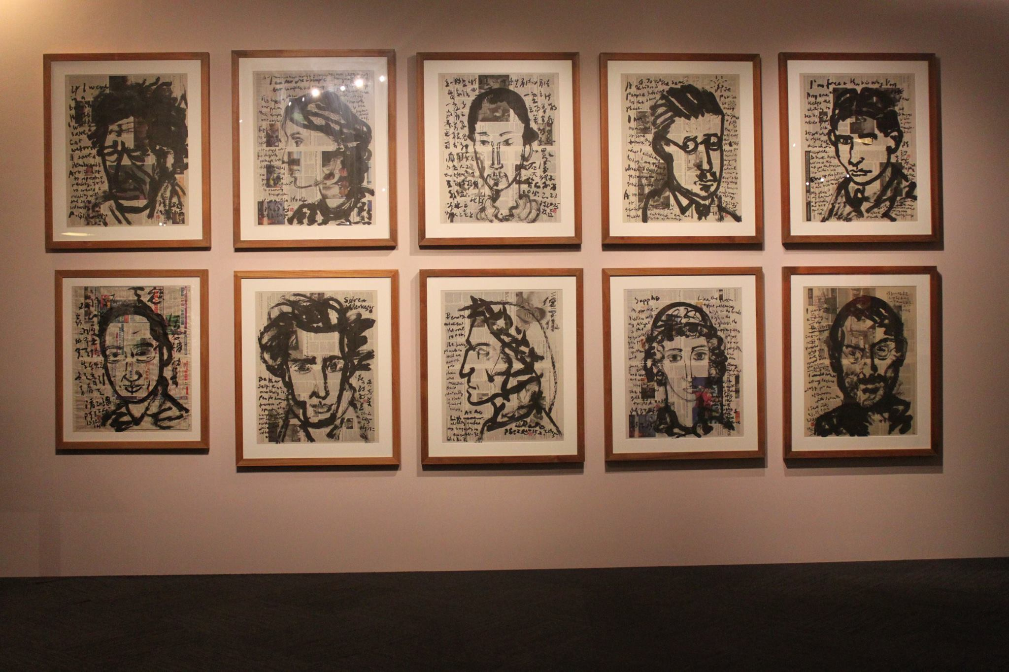 A photo of an exhibition wall. Ten ink portraits on newspapers are framed up and hung on the wall.