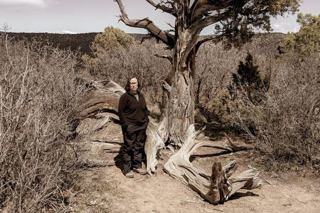 Len scowls while standing next to a tall juniper tree. All around her and the tree is a dense thicket of desert shrubs.