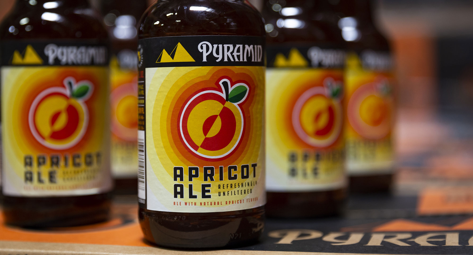 Closeup of an Apricot Ale bottle with more bottles blurred in the background