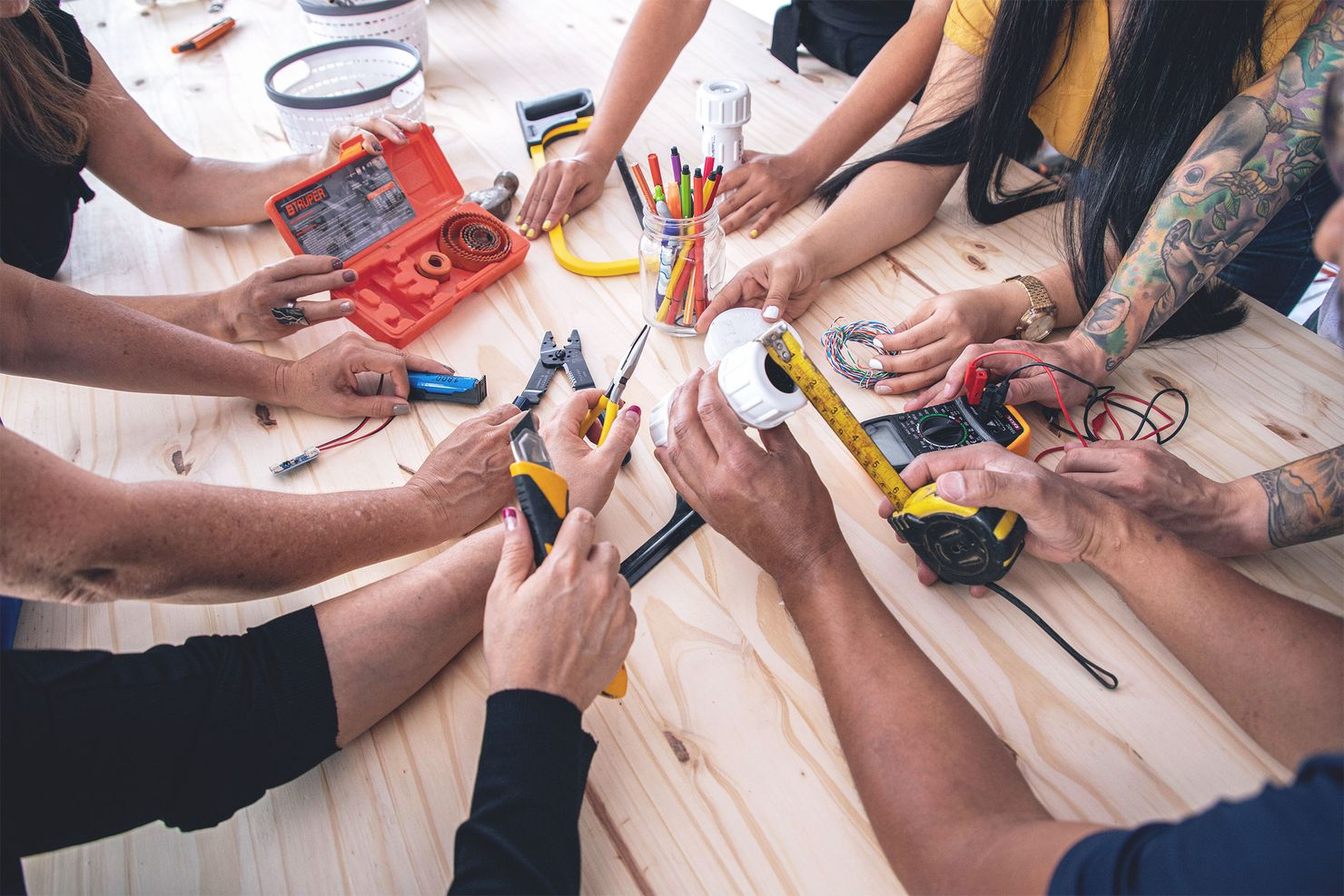 an over-the-shoulder view of the arms and hands of seven onsite workshop participants holding a variety of tools over a wooden workbench