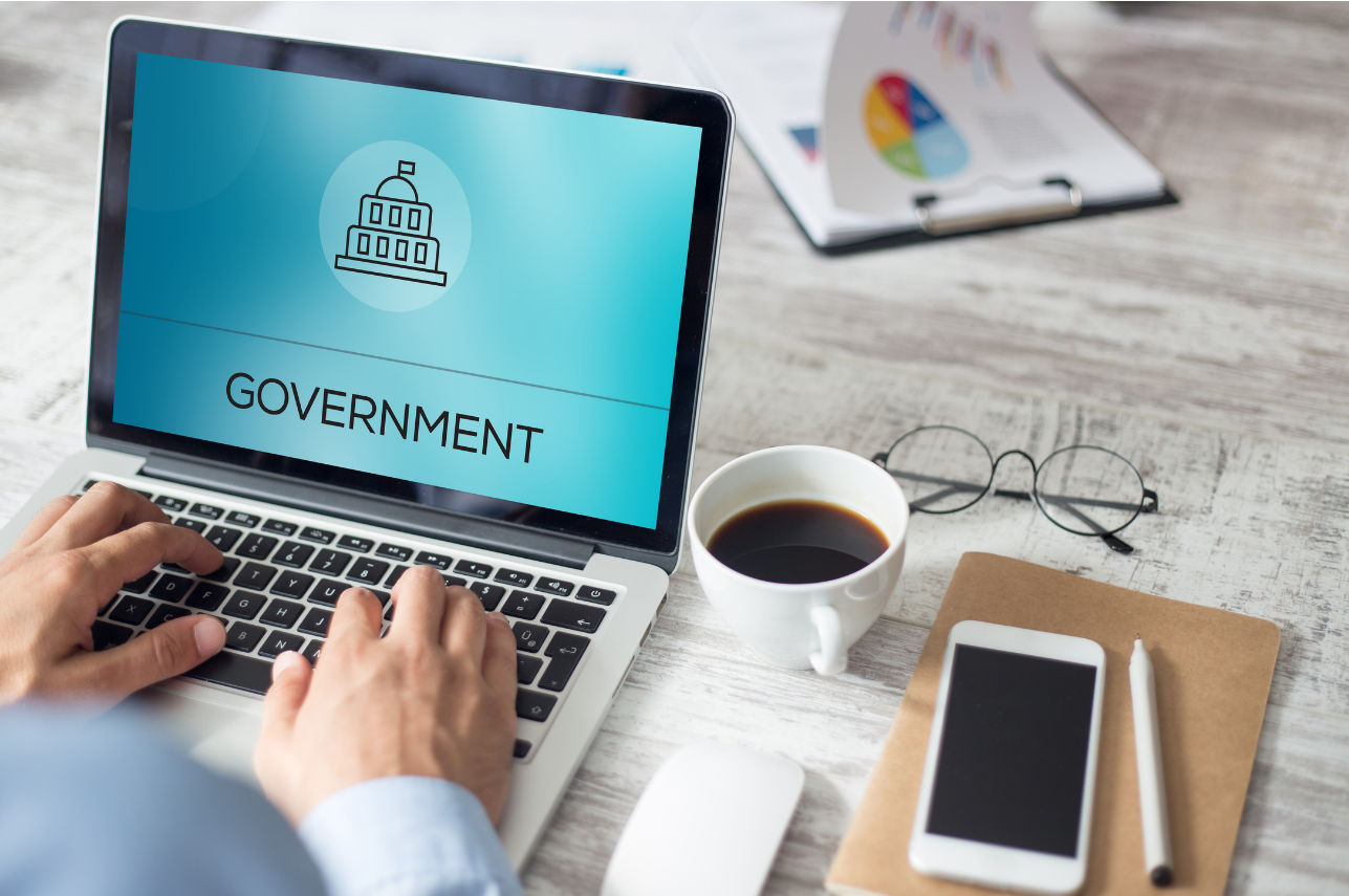 Text reading 'Government' and drawing of government building on light blue background on laptop computer screen. A person is typing on computer keyboard.