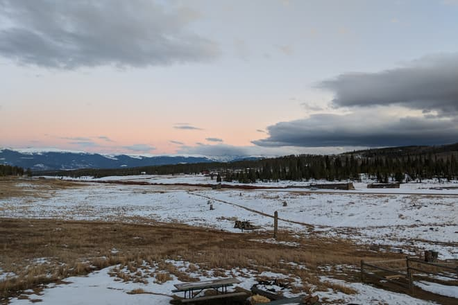 Looking out across a snowy high country ranch at sunset. In the distance, the Rocky Mountains.