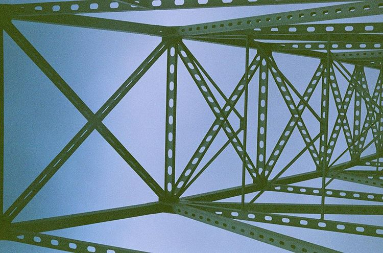 looking up through the green trusses of the Astoria-Megler bridge, with a light blue sky as the background.