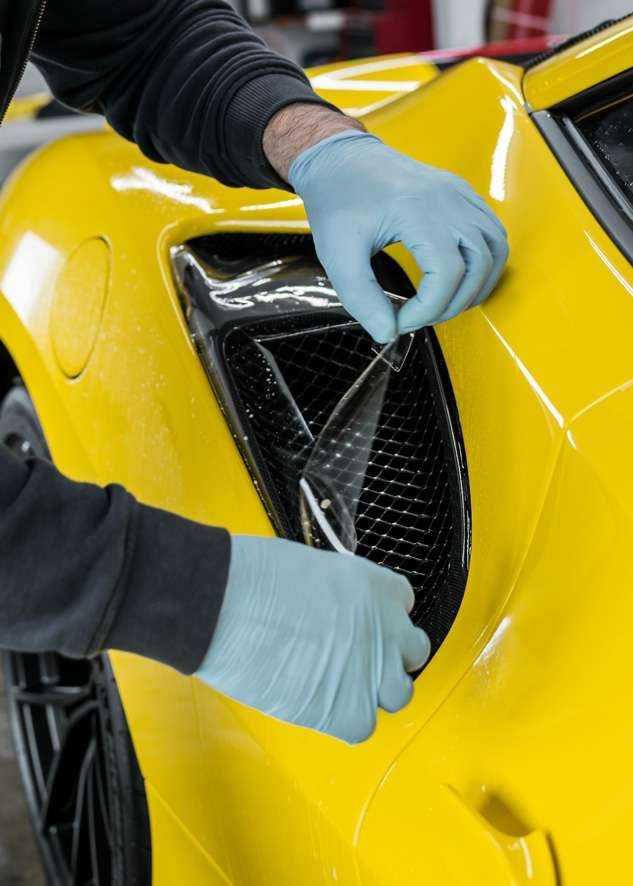 Paint protection film (PPF) being applied to side intake of yellow Ferrari 488 Pista