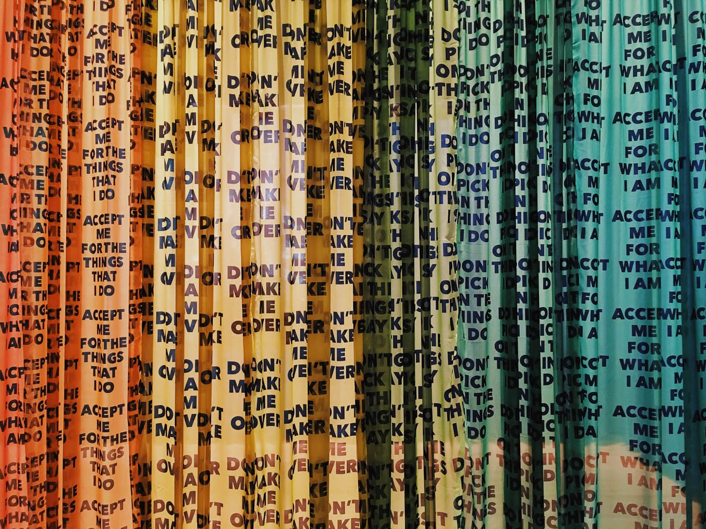 Thin vertical strips hanging with words written on them. The strips form a rainbow