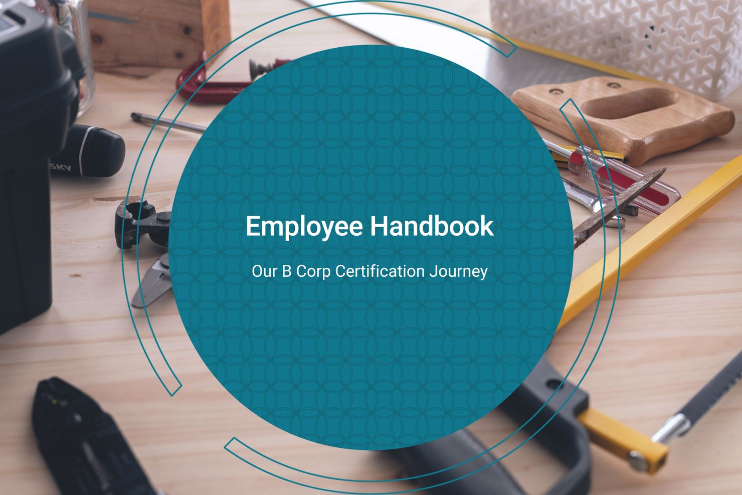 """a teal circle containing the text """"employee handbook"""" overlays a photo of a wooden workbench covered in tools"""