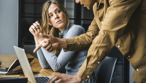 Woman client in grey looks at man accountant in yellow shirt who is pointing at laptop on wooden desk whilst using 4 ways to nail advisory a list by Futrli #advisory